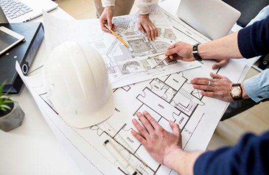 arquitectos-ingeniero-discutiendo-mesa-blueprint_23-2147842977